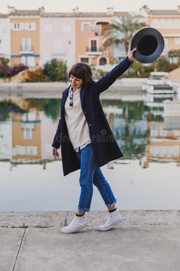 Extérieur de portrait d'une jeune belle femme avec les vêtements élégants posant avec un chapeau moderne lifestyle fond de port e photographie stock