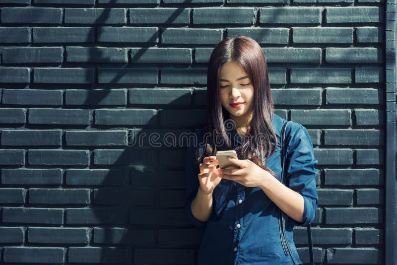 Extérieur debout de jeune femme asiatique contre le mur de briques peint, u photographie stock libre de droits