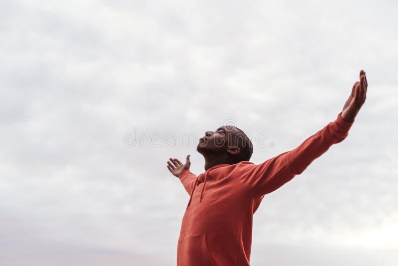 Extérieur debout de jeune homme africain seul embrassant la nature photographie stock libre de droits