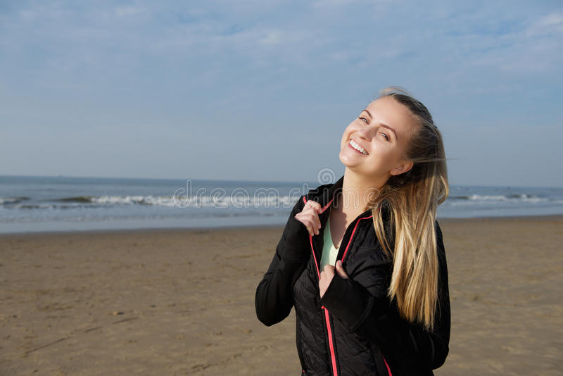 Extérieur debout de sourire de fille de forme physique sur la plage photo stock