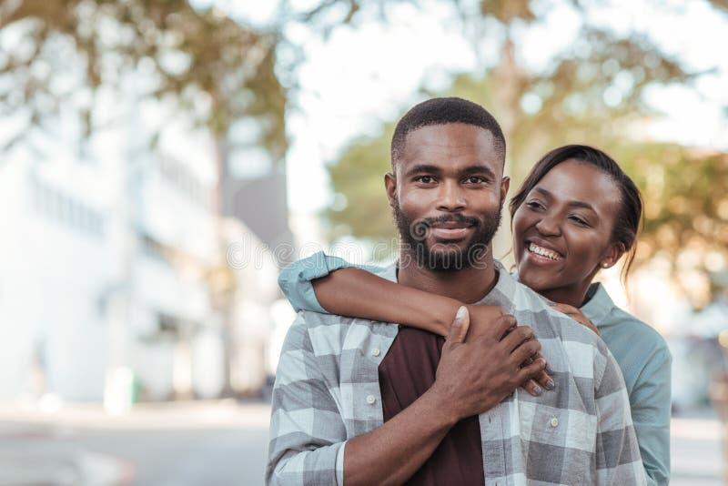 Extérieur debout de sourire de jeunes couples africains un jour ensoleillé photos stock