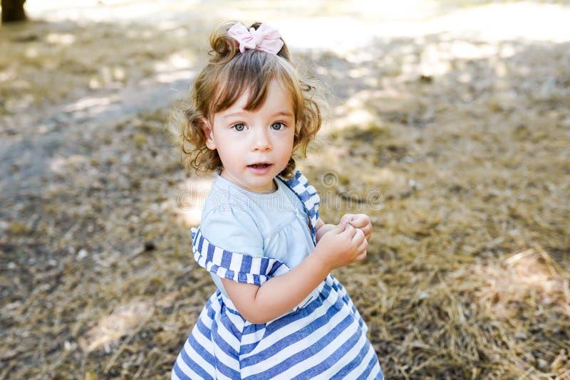 Extérieur doux de petite fille avec les cheveux bouclés dans le vent, marchant en parc, l'espace de copie images stock
