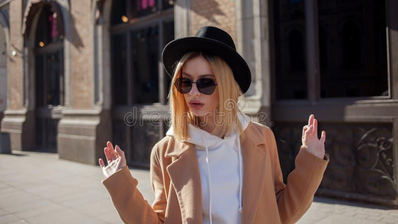 Extérieur heureux de fille, jour ensoleillé Jeune femme à la mode et à la mode dans le chapeau de feutre noir et le manteau b images libres de droits