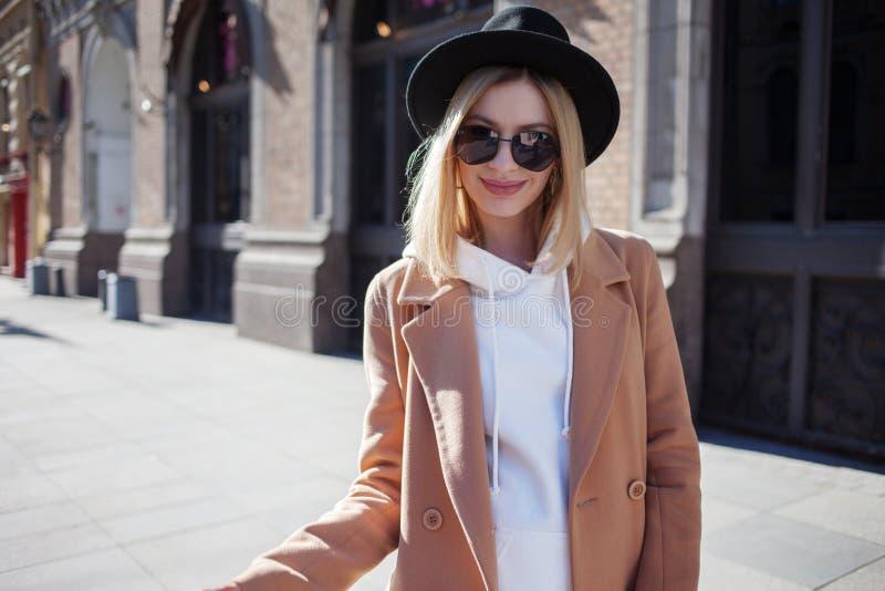 Extérieur heureux de fille, jour ensoleillé Jeune femme à la mode et à la mode dans le chapeau de feutre noir et le manteau b photo libre de droits