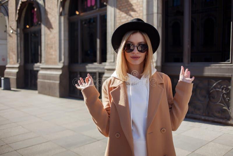 Extérieur heureux de fille, jour ensoleillé Jeune femme à la mode et à la mode dans le chapeau de feutre noir et le manteau b photos stock