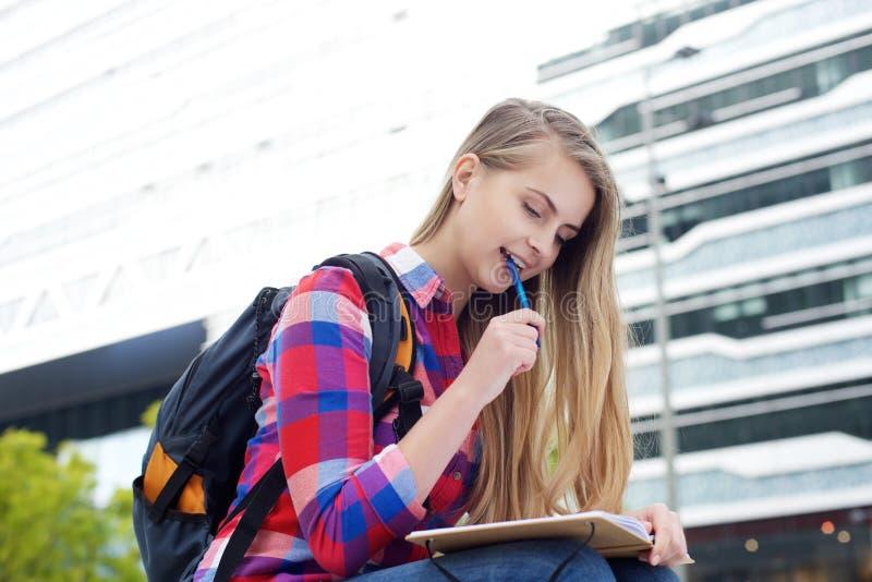 Extérieur se reposant d'étudiant étudiant avec le stylo et le livre photo libre de droits