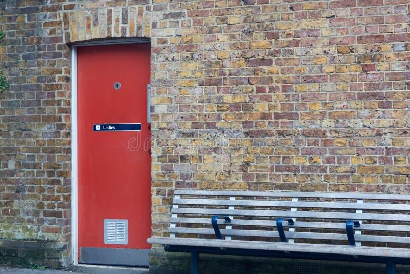 Extasie ao toalete do ` s das mulheres porta vermelha em uma parede de tijolo fotografia de stock