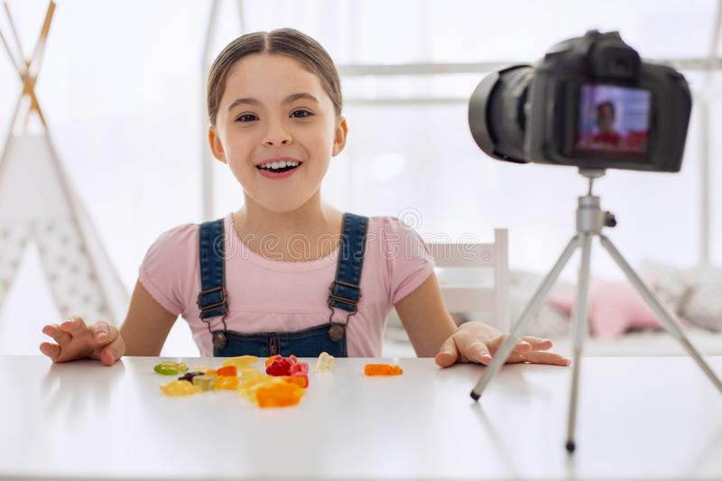 Extatisch meisje die terwijl het eten gummies op camera stellen royalty-vrije stock afbeeldingen