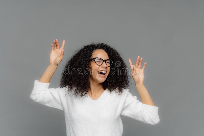 Extatische Afro de Amerikaanse vrouw handen opheft, lacht gelukkig, geniet van prettige muziek, draagt optische glazen en witte t royalty-vrije stock foto