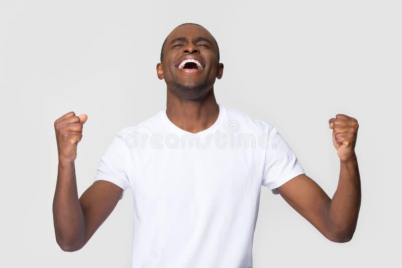 Extatische gelukkige jonge Afrikaanse Amerikaanse mens zegevierend het vieren winst royalty-vrije stock foto