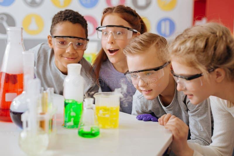 Extatische tienerstudenten die definitief stadium van chemisch experiment waarnemen stock afbeelding
