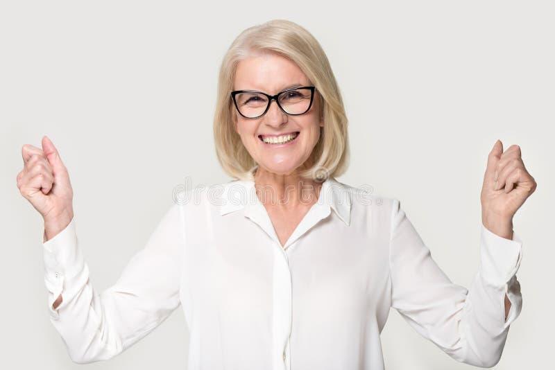 Extatisk hög kvinna som firar framgång som poserar på grå studiobakgrund royaltyfri foto