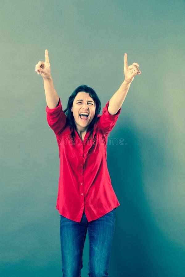 Extatisk kvinna som skrattar med utåtriktad handgest arkivbild