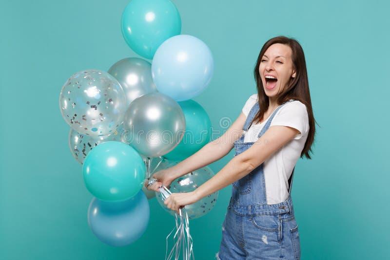 Extatisk lycklig rolig ung kvinna i grov bomullstvillkläder som skriker, firar och rymmer färgrika luftballonger isolerade på fotografering för bildbyråer