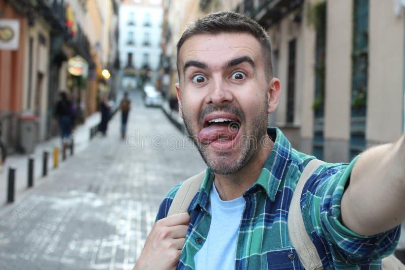 Extatisk man som utomhus tar en selfie royaltyfri bild