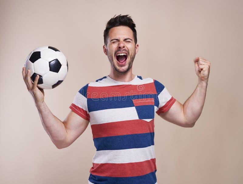 Extatisk manlig fan med att hurra för fotbollboll royaltyfri bild
