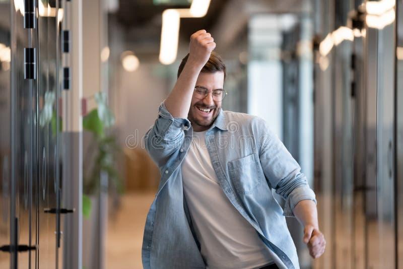 Extatisk manlig vinnare som i regeringsställning dansar hallet som skrattar fira framgång royaltyfri bild