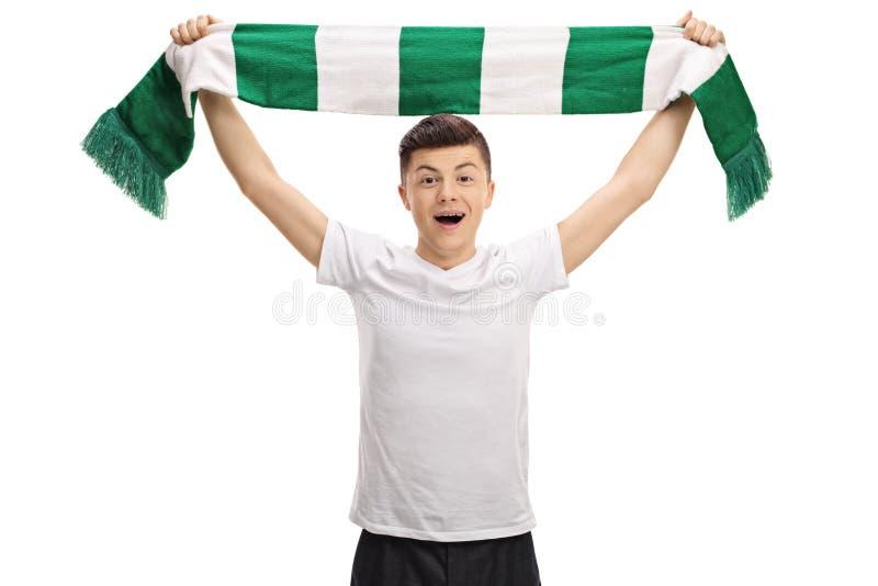 Extatisk tonårs- fotbollsfan som rymmer en halsduk arkivbild