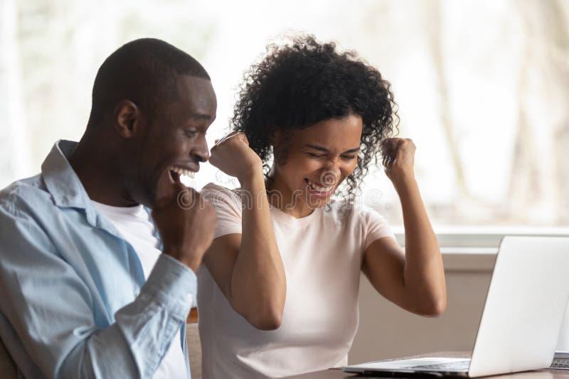 Extatiska afrikanska par firar online-seger sitter på tabellen royaltyfria bilder