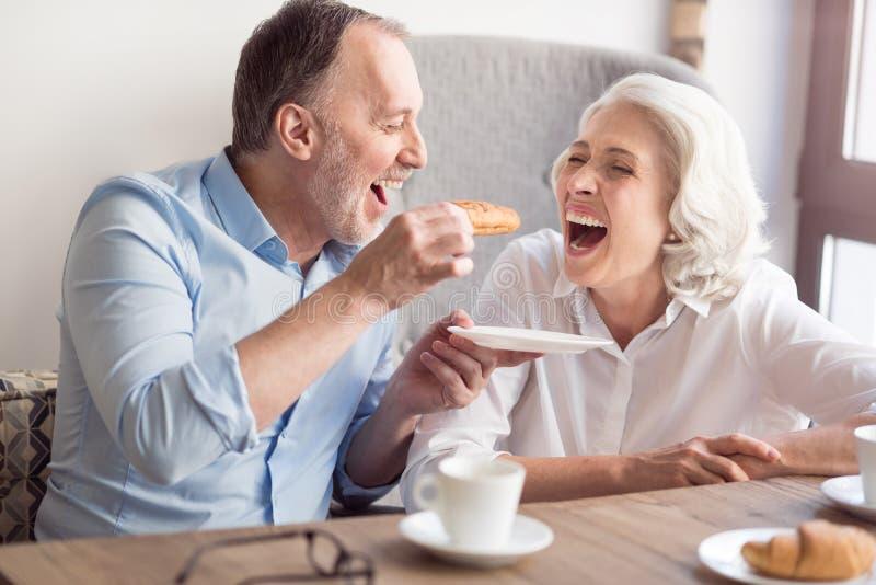 Extatiska höga par som har lunch i kafét royaltyfria foton