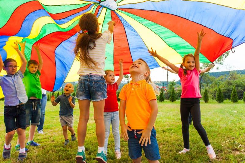 Extatiska ungar som studsar under regnbågemarkistextilen fotografering för bildbyråer