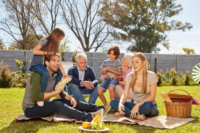 Extended family is having picnic or party in the garden. Extended family with children and grandparents picnic or party in the garden stock image