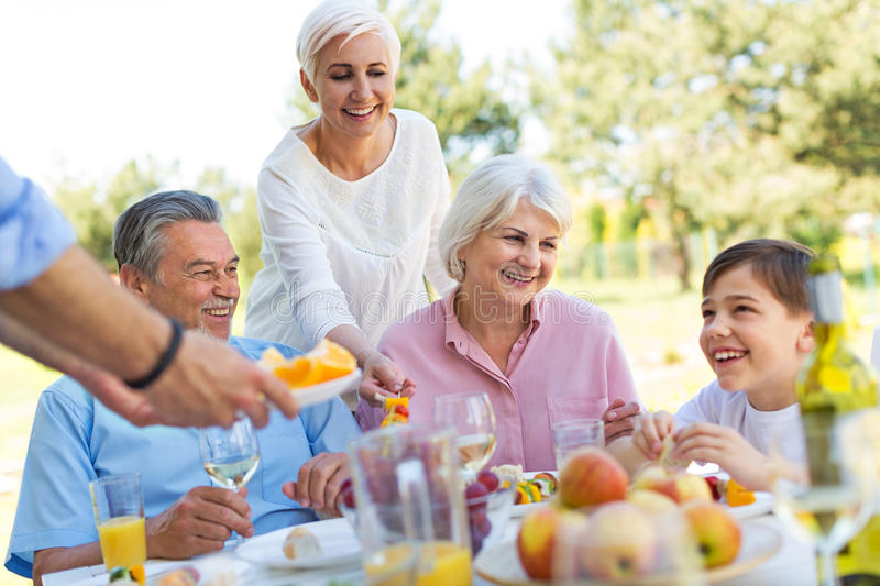 Extended family eating outdoors stock photography