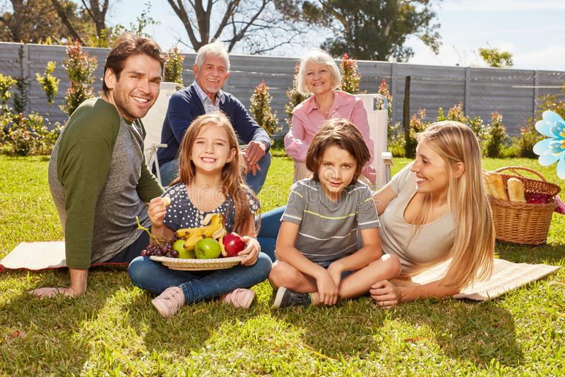 Extended family is having a picnic in summer in the garden stock image