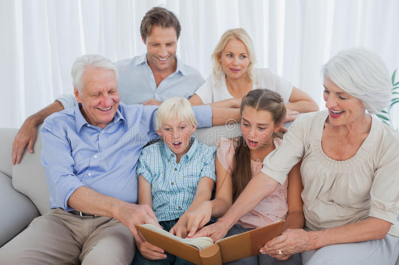 Extended Family Looking At Their Album Photo Stock Photography