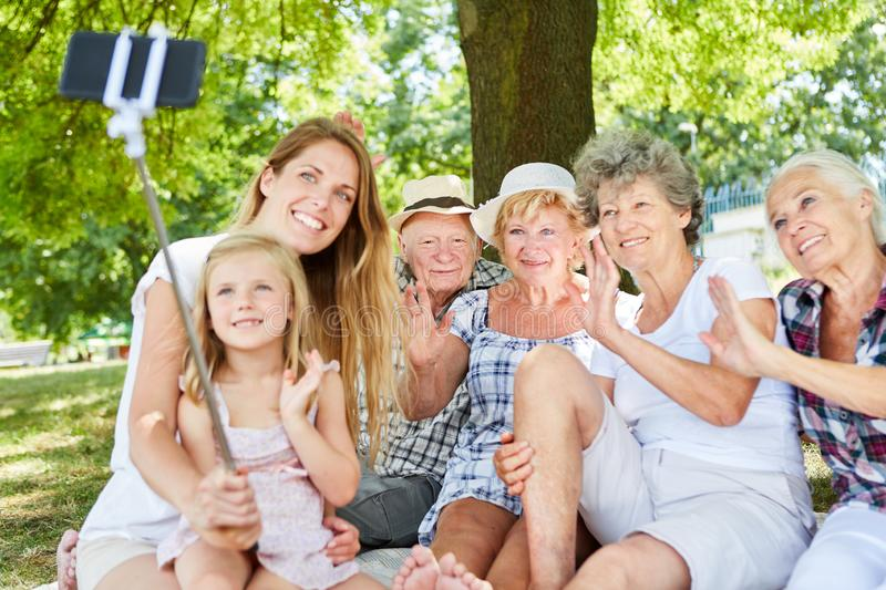 Extended family makes selfie with selfie stick stock photo