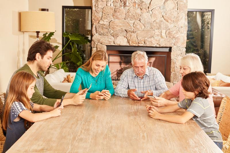 Extended family playing with tablet and smartphone. Extended family playing and surfing with tablet and smartphone together at the table royalty free stock photo