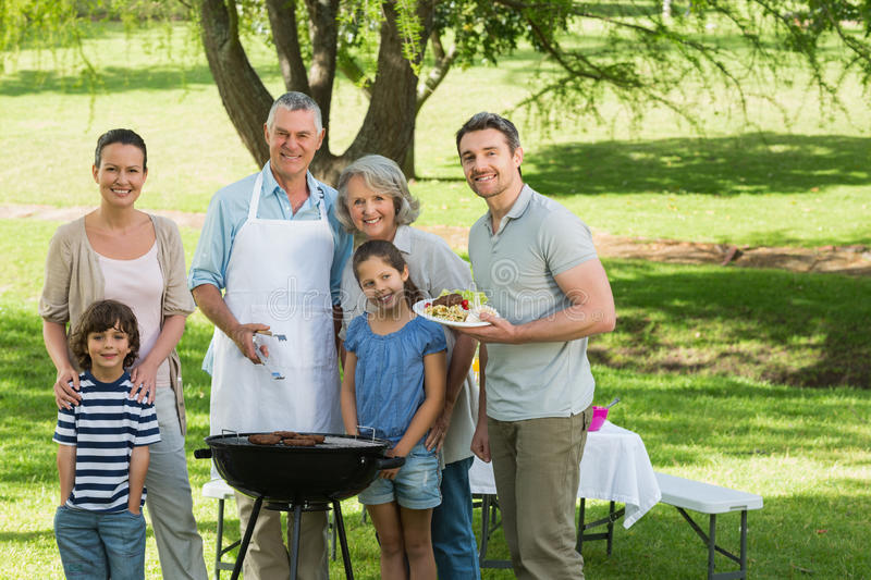 Extended family standing at barbecue in park. Portrait of an extended family standing at barbecue in the park stock photo