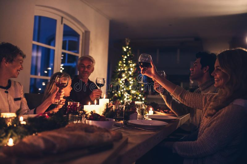 Extended family toasting wine at christmas dinner stock photos