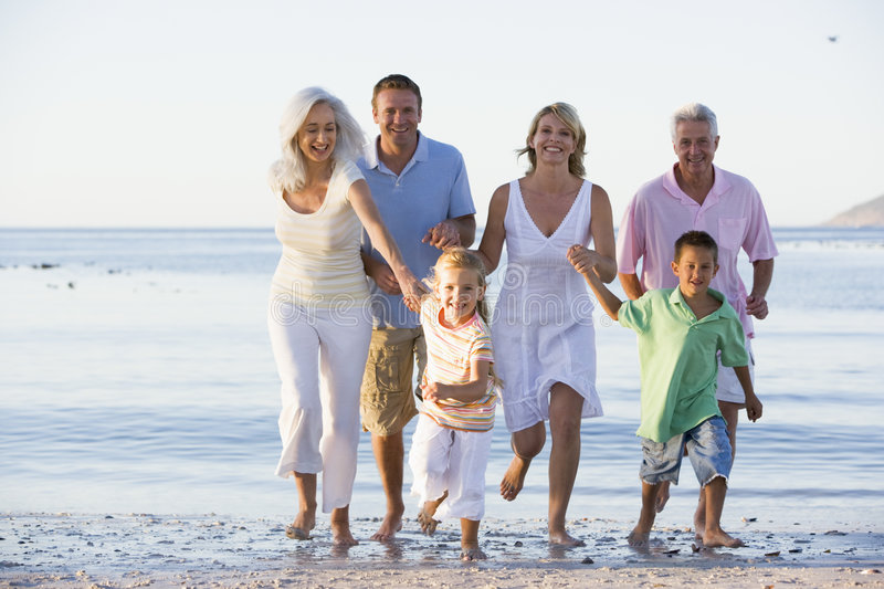 Extended family walking on beach stock photos