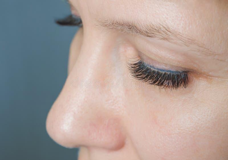 Extensão da pestana O olho de uma mulher com chicotes fotos de stock royalty free