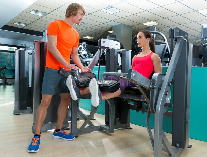 Extensão do pé da mulher do Gym com instrutor pessoal fotos de stock royalty free