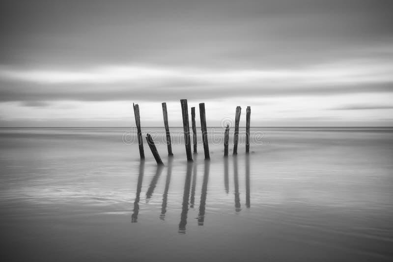 Extensões de madeira velhas longas da ponte do cais da praia ao mar Céu nebuloso profundo após a tempestade grande Expectativa ao imagem de stock royalty free