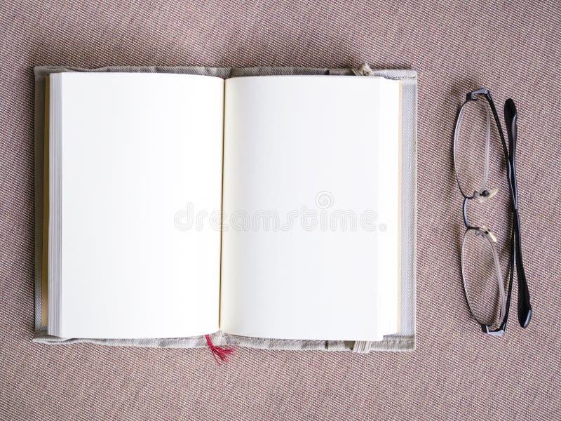 Extensión abierta de la página en blanco del libro con las lentes en la tabla foto de archivo