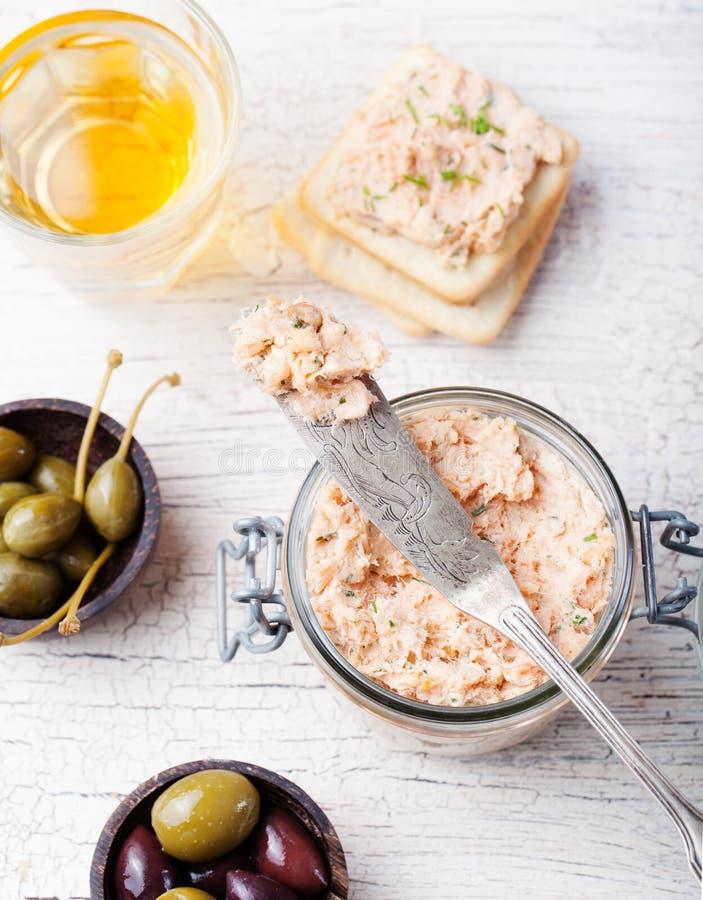 Extensión del salmón ahumado y de queso suave, crema batida, coronilla en un tarro con las galletas y alcaparras en un fondo de m imagen de archivo libre de regalías
