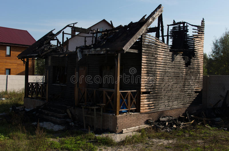 Extensive Fire Damaged Real Estate Property. Extensive Fire Damage of Architectural Real Estate Property on Grassy Landscape Caused by Negligence royalty free stock photos