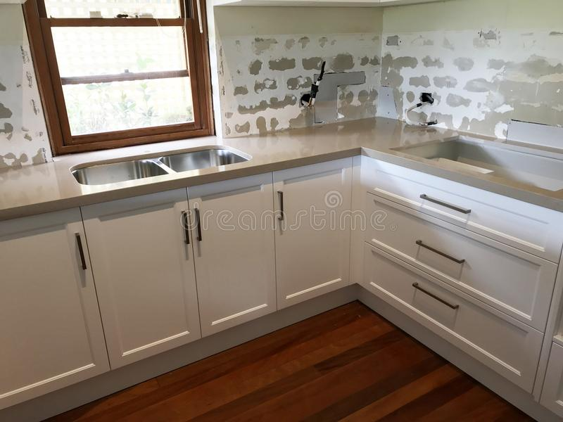 High Quality Extensive Kitchen Renovations. Extensive kitchen renovation with new stone bench tops, white cupboards, and white sub way tiles with wooden royalty free stock image