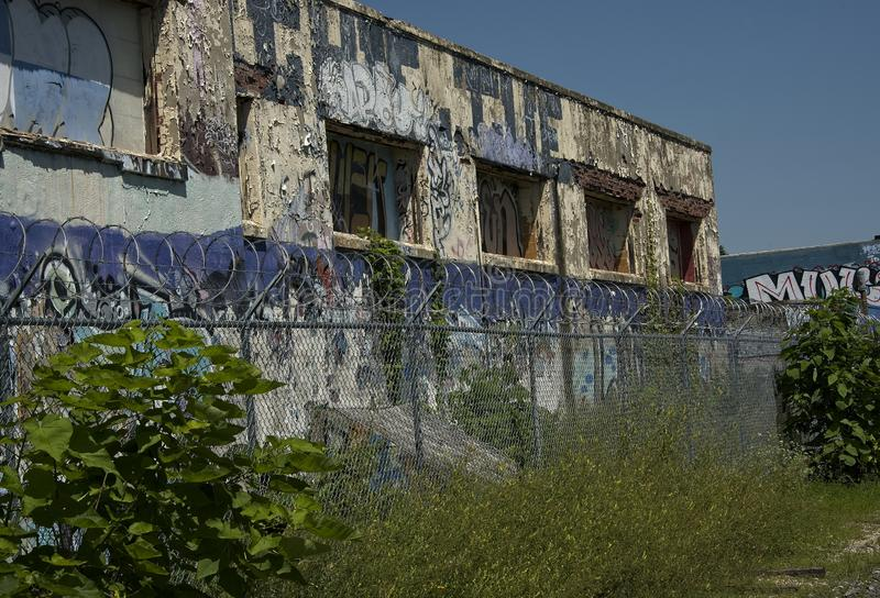 Abandoned Industrial Building with Graffiti and Barbed Wire Fence stock photography