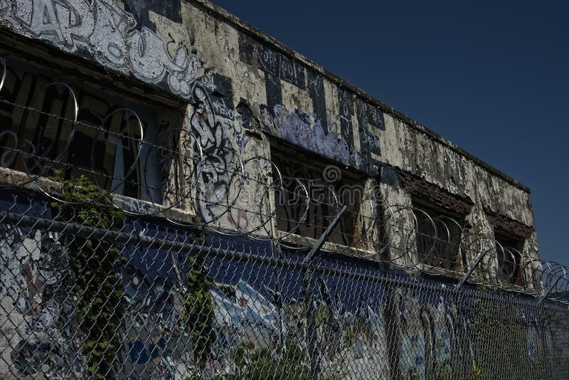 Abandoned Industrial Building and Barbed Wire Coils Horizontal royalty free stock photos