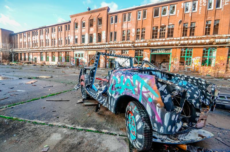 An exterior of an antique vintage roofless, roadster patterned car parked in front of an old school building in Berlin, Germany. An exterior of an antique stock images