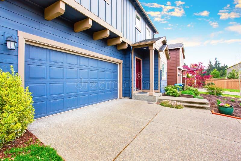 Exterior azul de la casa Vista del garaje y del pórtico con la puerta de entrada roja foto de archivo libre de regalías