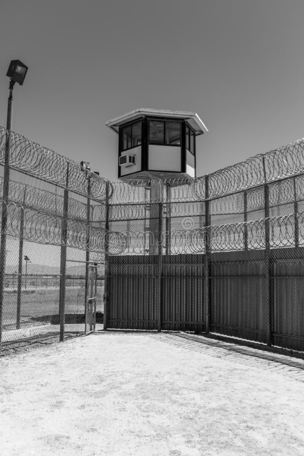 Exterior vertical shot of prison yard with guard tower. Exterior black and white vertical shot of prison yard with guard tower stock photography