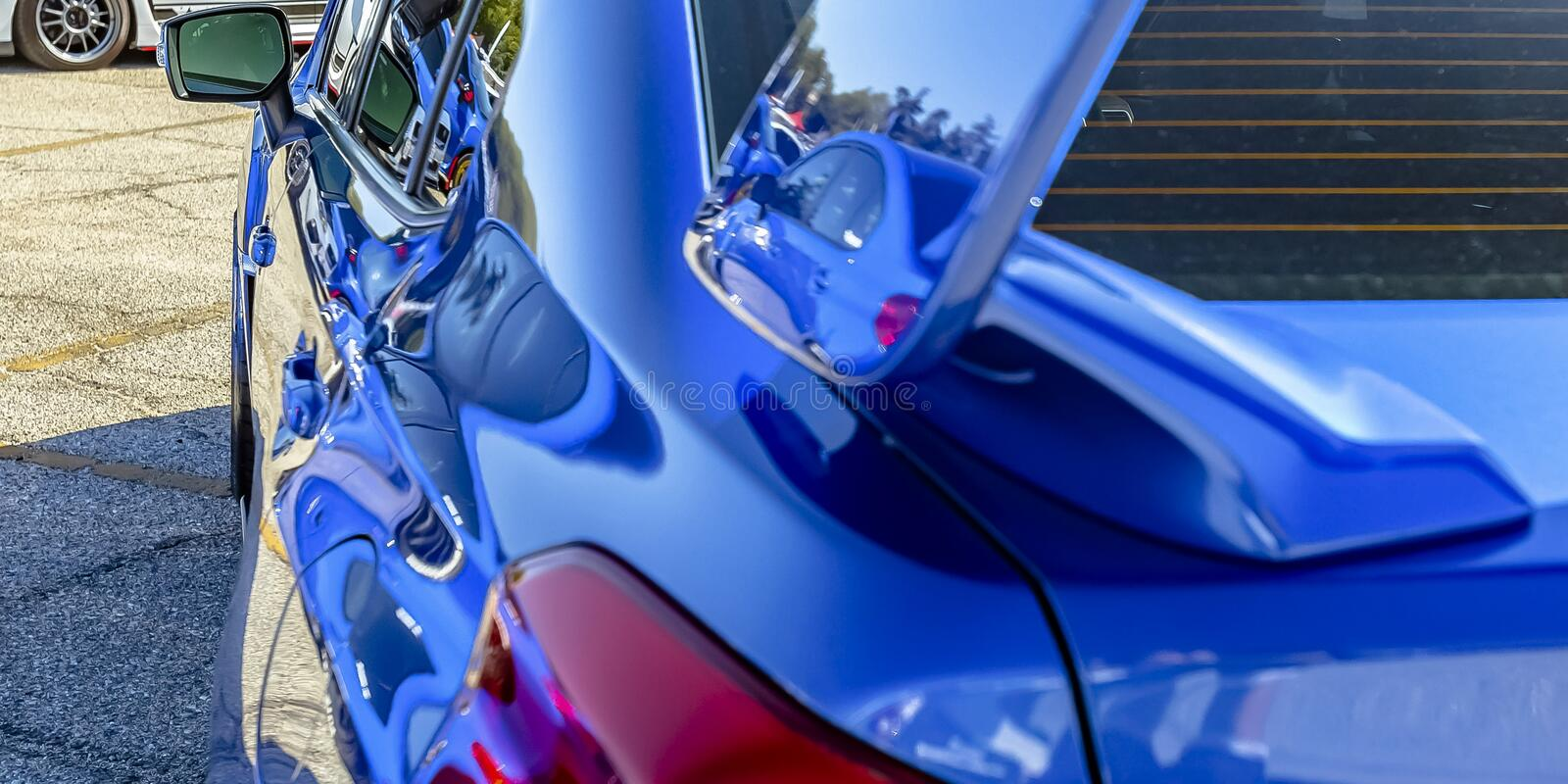 Exterior of a blue car reflecting sunlight. View of the back and side of a blue car with red taillight and black framed side mirror. Sun rays bounces off the royalty free stock photo