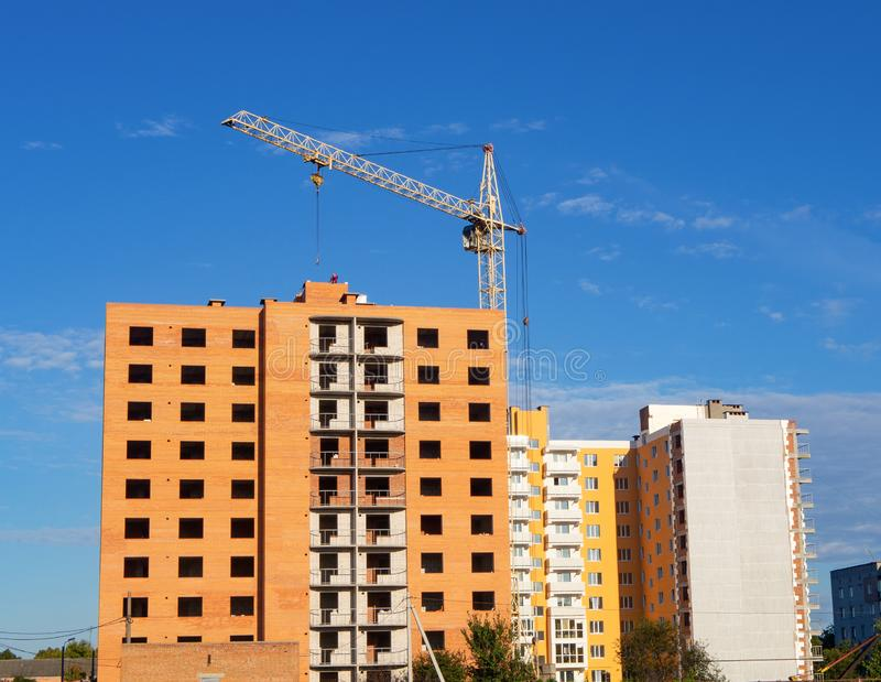 Exterior of brick multistory residential building under construction with holes for windows and balconies. Affordable housing stock image