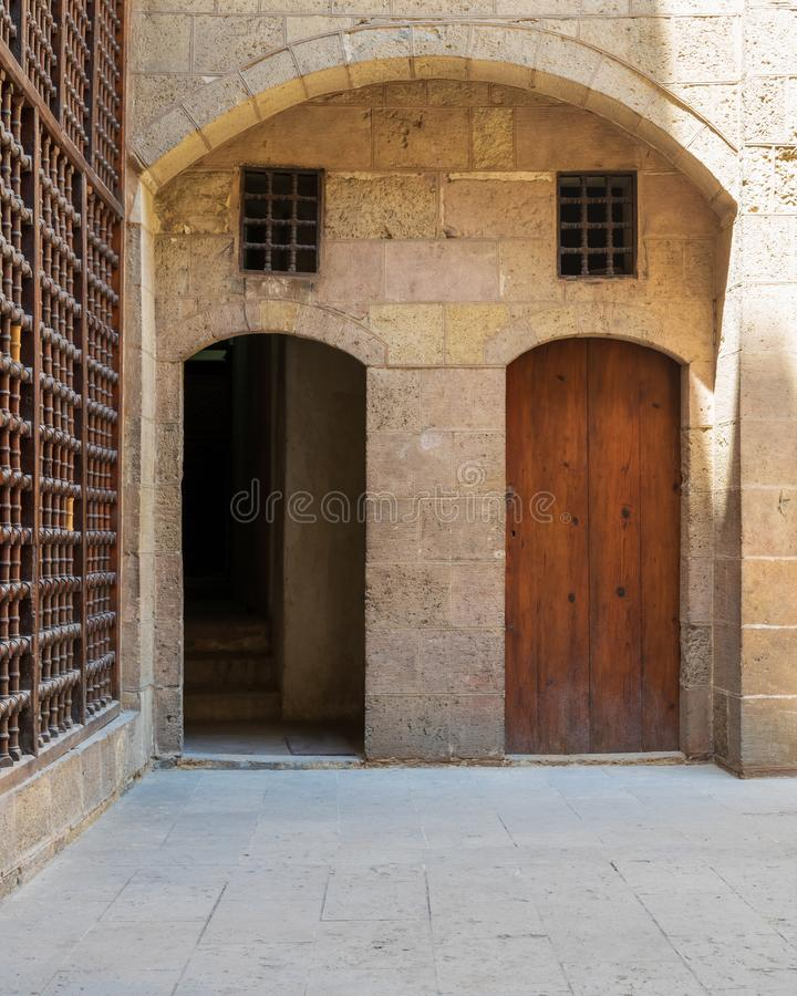 Exterior brick stone passage with two adjacent vaulted wooden grunge doors. Exterior brick stone passage with two adjacent vaulted opened and closed wooden royalty free stock photos