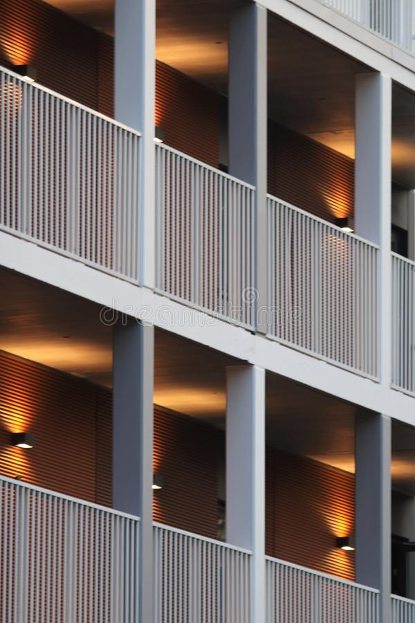 An exterior of a building with beautiful lights. A photo of an exterior of a block of flats in the evening when the night is falling. The lights cast beautiful stock image